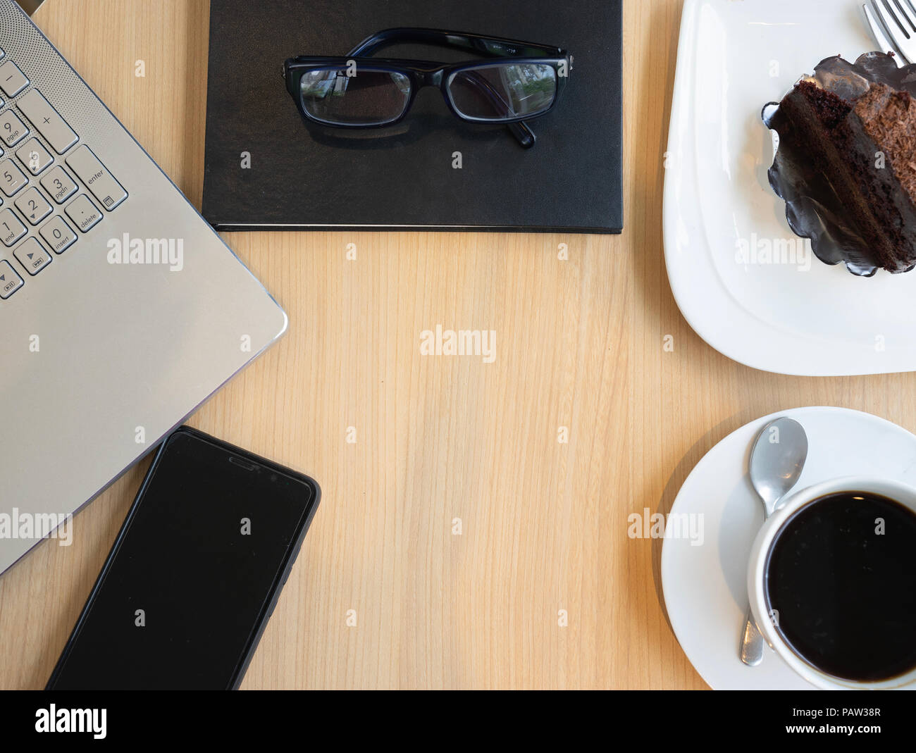 Laptop Mobile Phone Coffee Cup Chocolate Cake And Glasses On Wooden Table Top View With Work Space Design Stock Photo Alamy