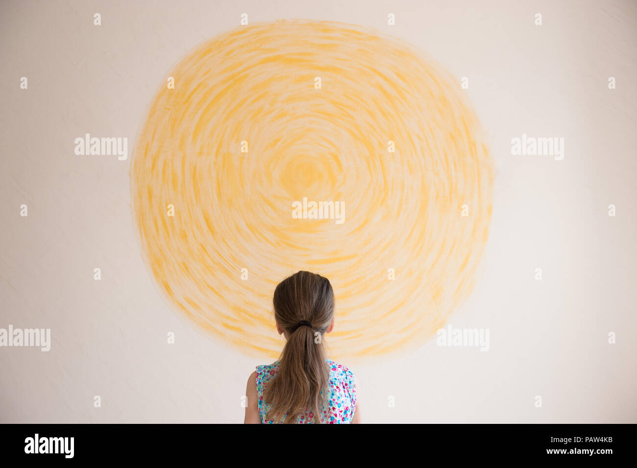 little caucasian girl looking at yellow sun painted on wall indoors - Stock Image
