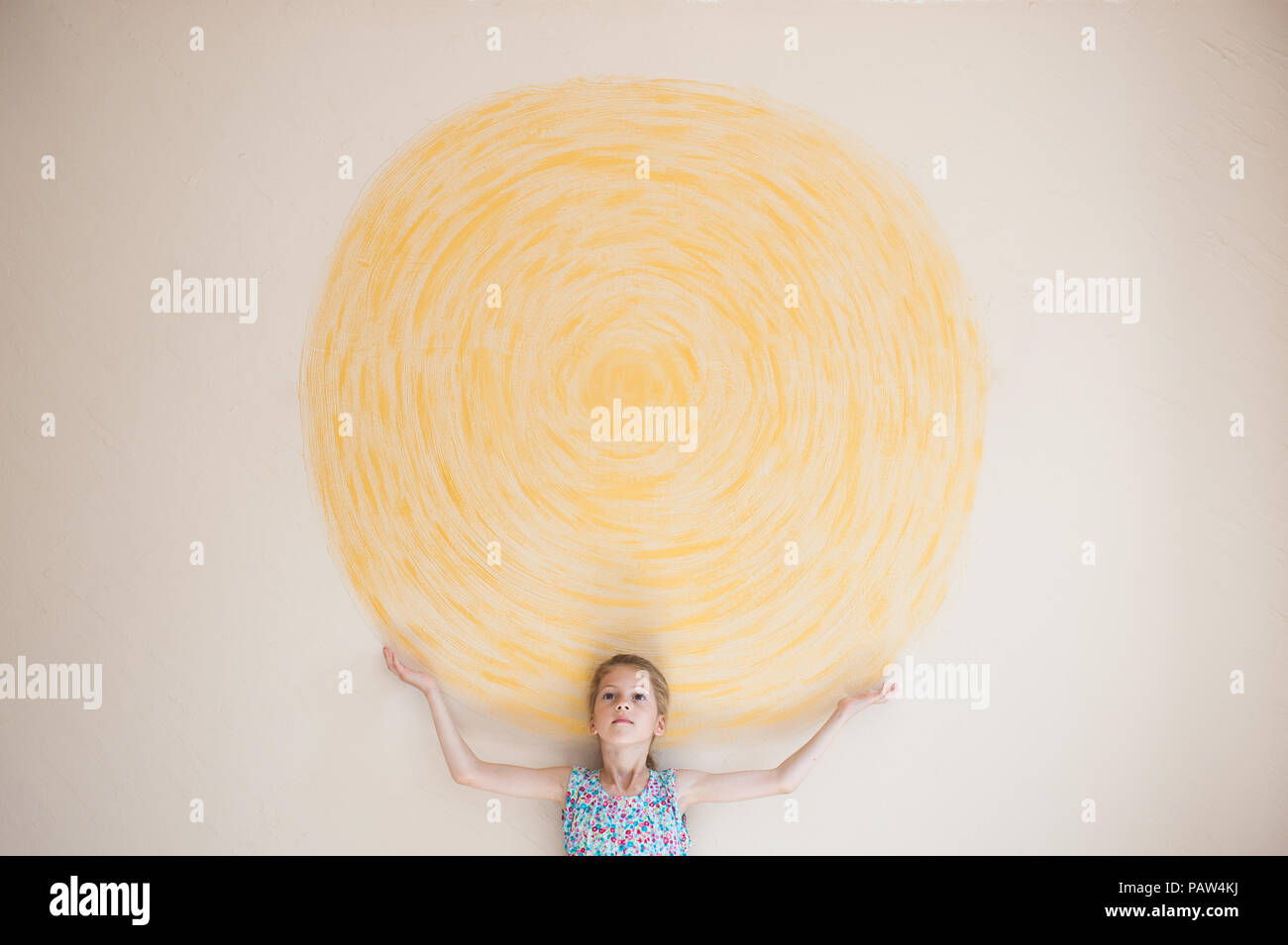 concept of beautiful caucasian girl holding sun painted on yellow wall indoors - Stock Image