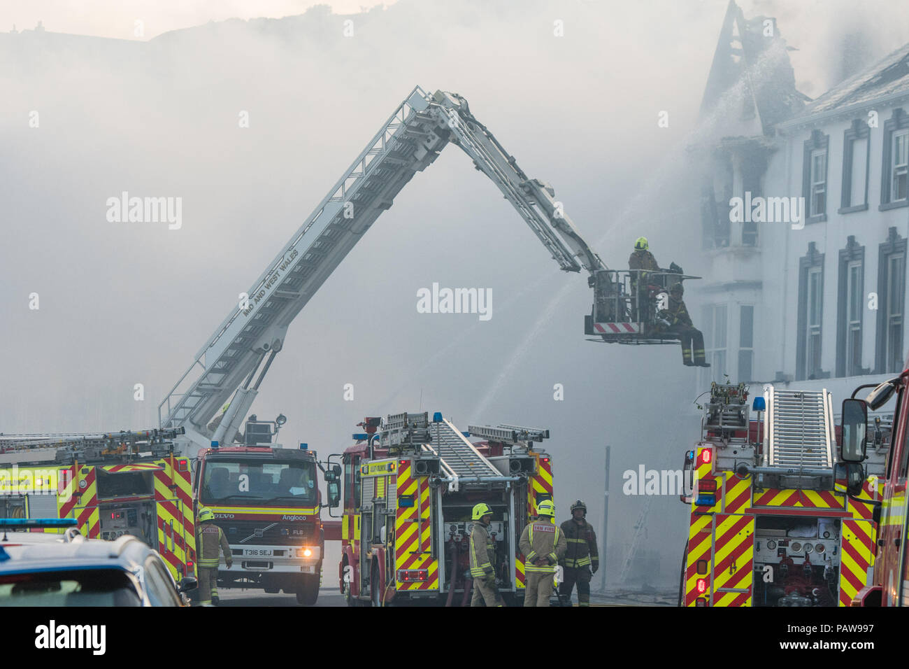 Aberystwyth Wales UK, Wednesday 25 July 2018  A major fire has severely damaged two adjoining hotels on Aberystwyth seafront. The Belle Vue hotel and the Belgrave House Hotel caught fire at around 2am this morning, Fire engines from all over Mid and west wales have been in attendance throughout the night. There are no reports of casualties, and all the guests have been transferred to other accommodation . Much of the centre of the town has been cordoned off for safety reasons   photo credit : keith morris/Alamy Live News - Stock Image