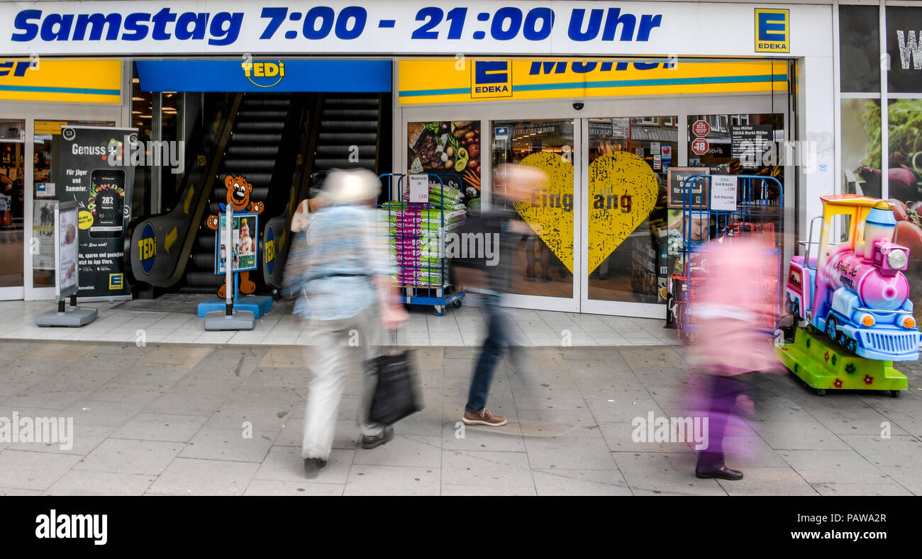 Germany, Hamburg. 23rd July, 2018. Passers-by walk past the supermarket where the so-called Barmbek assassination attempt took place a year ago. Credit: Axel Heimken/dpa/Alamy Live News - Stock Image