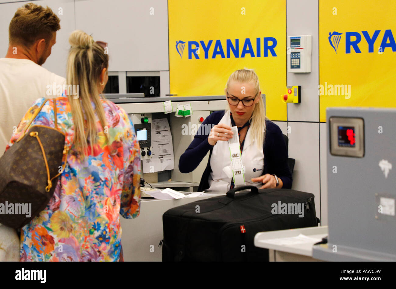 Mallorca, Spain.  25 July 2018, Mallorca, Spain: Airport employee attaches a luggage tag to a Ryanair check-in counter at Palma de Mallorca airport. The start of a two-day strike by cabin crew at the low-cost airline Ryanair has caused great displeasure among countless travellers in several European countries. The most cancellations occurred in Spain, where Ryanair cancelled 200 flights - just under a quarter of all connections. Credit: dpa picture alliance/Alamy Live News - Stock Image