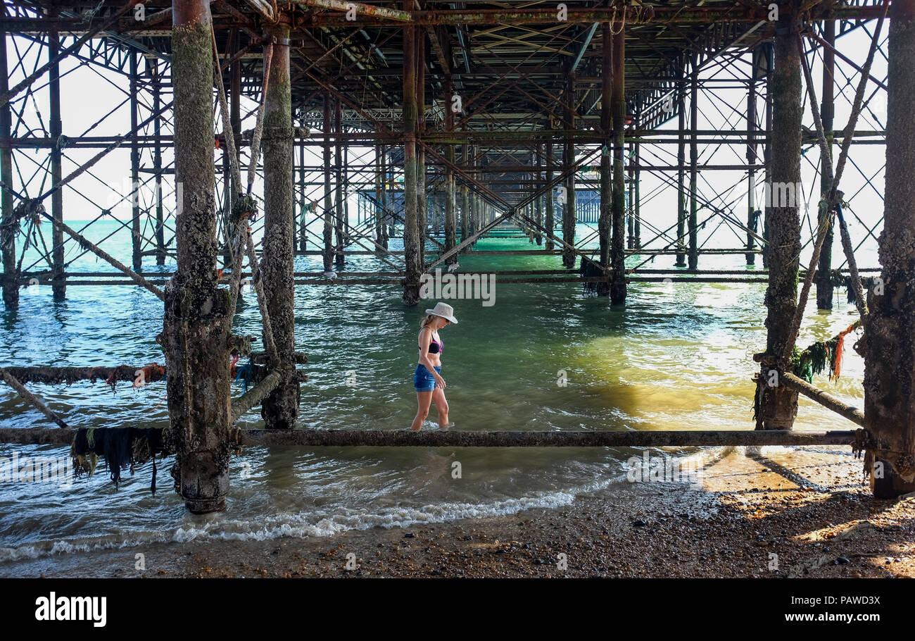 Brighton UK 25th July 2018 - A woman walks under the Brighton Palace Pier to stay in the shade as the heatwave conditions continue on the south coast with the hottest day so far predicted to be tomorrow in the UK Credit: Simon Dack/Alamy Live News Stock Photo