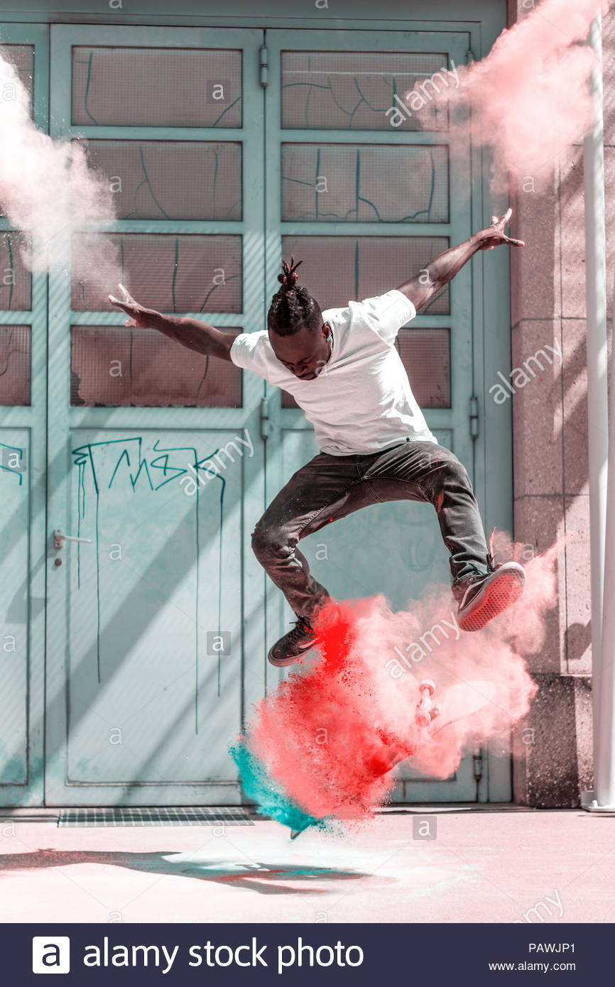Man jumping in mid air over skate board with colorful powder paint - Stock Image