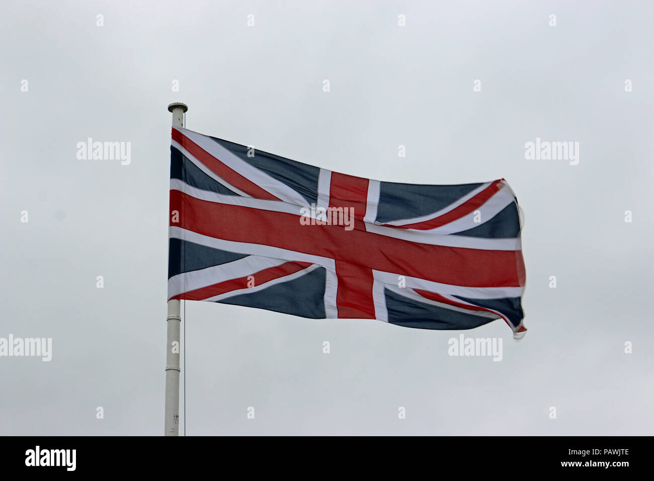 Union Jack flag fluttering in the wind on a white flagpole with a grey sky background. - Stock Image