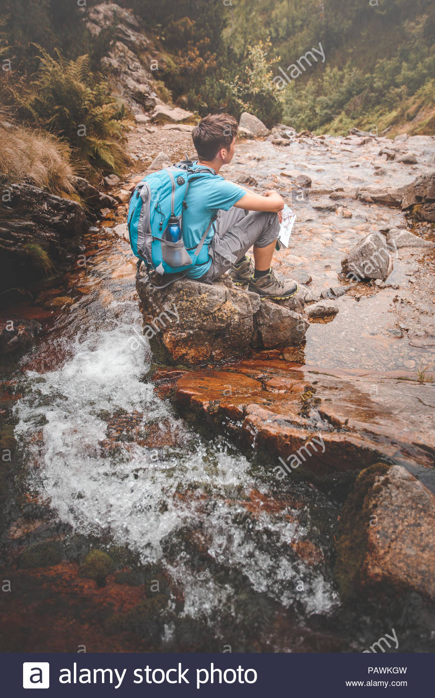 Boy sitting on a rock on mountain trail - Stock Image