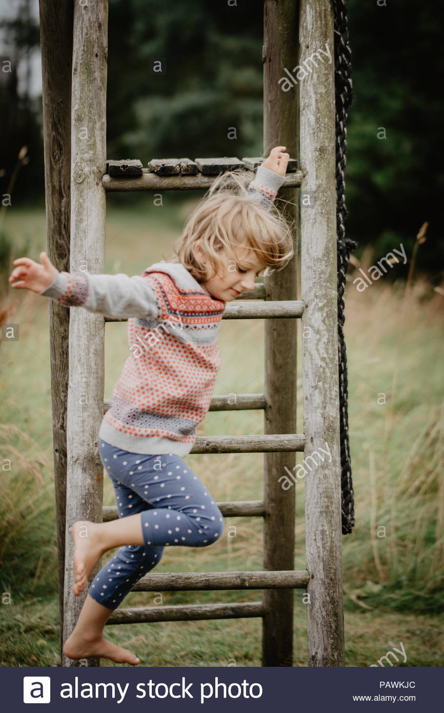 Action shot of a girl playing in a field - Stock Image