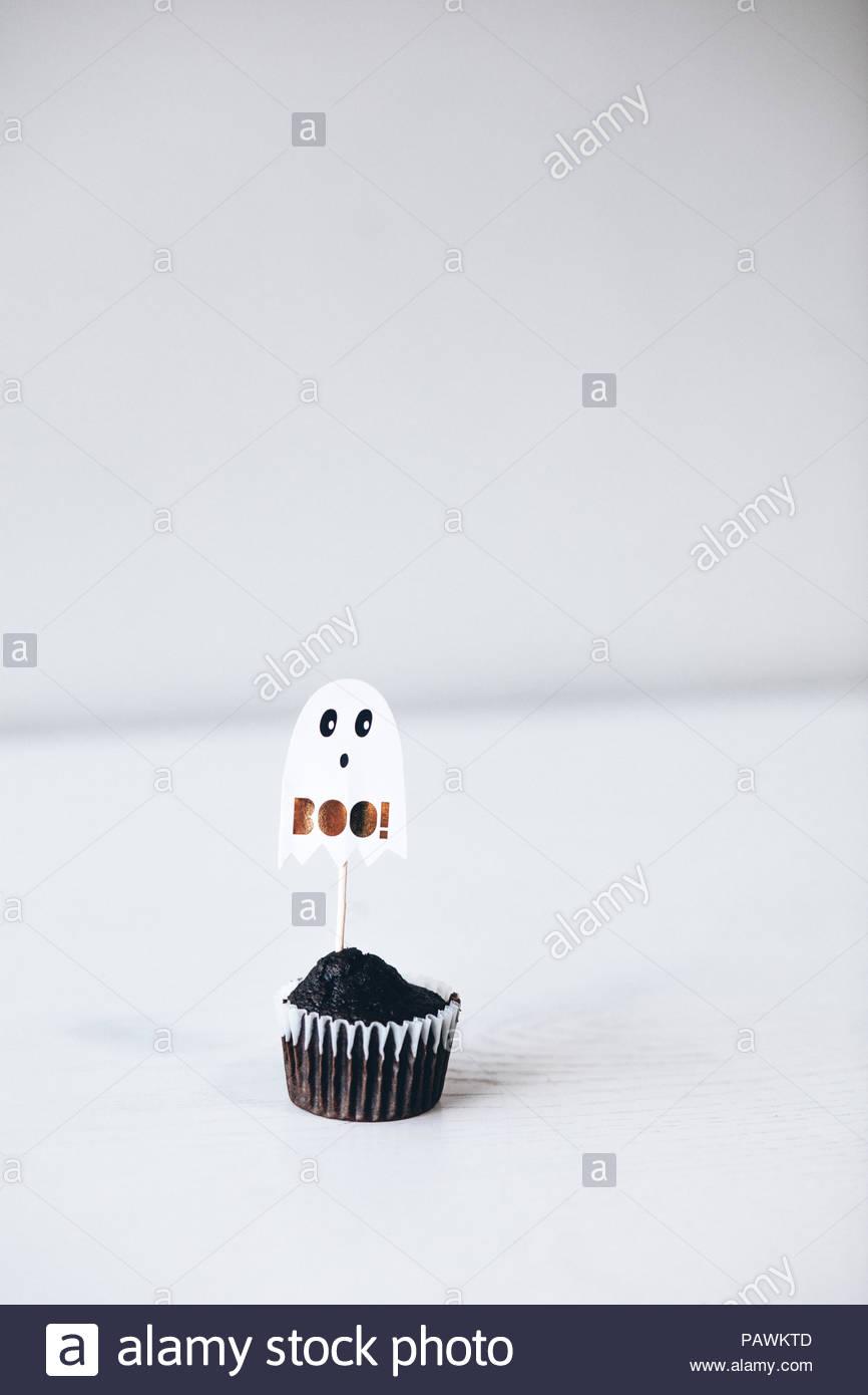 Halloween chocolate cupcake on white background - Stock Image