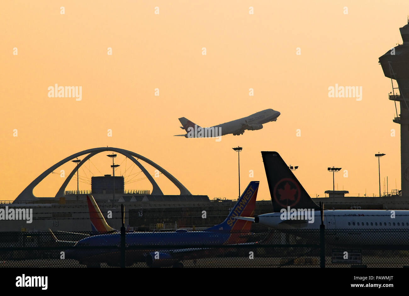 Boeing 747 taking off past LAX Theme Building - Stock Image