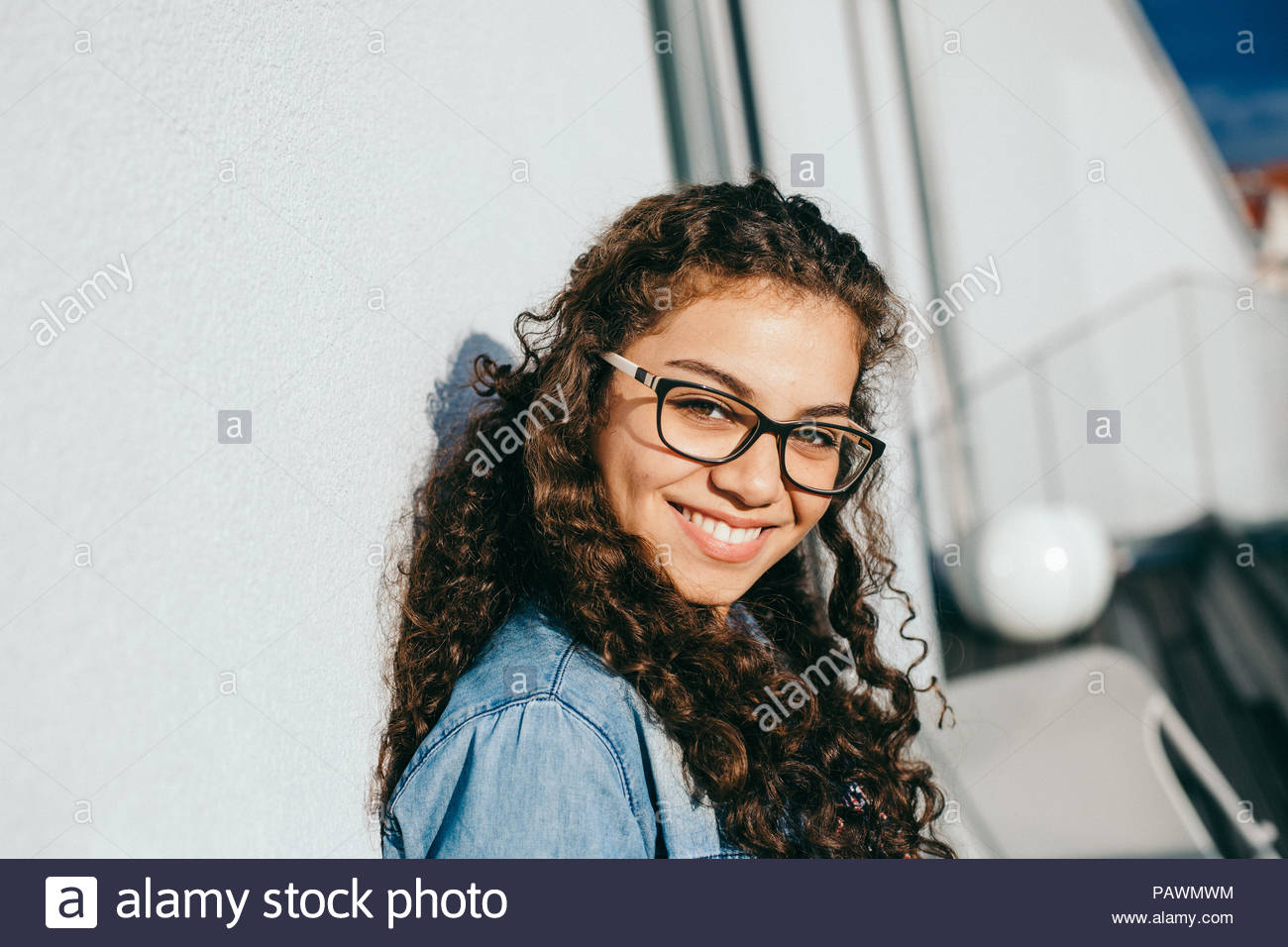 Smiling woman with curly hair and glasses - Stock Image