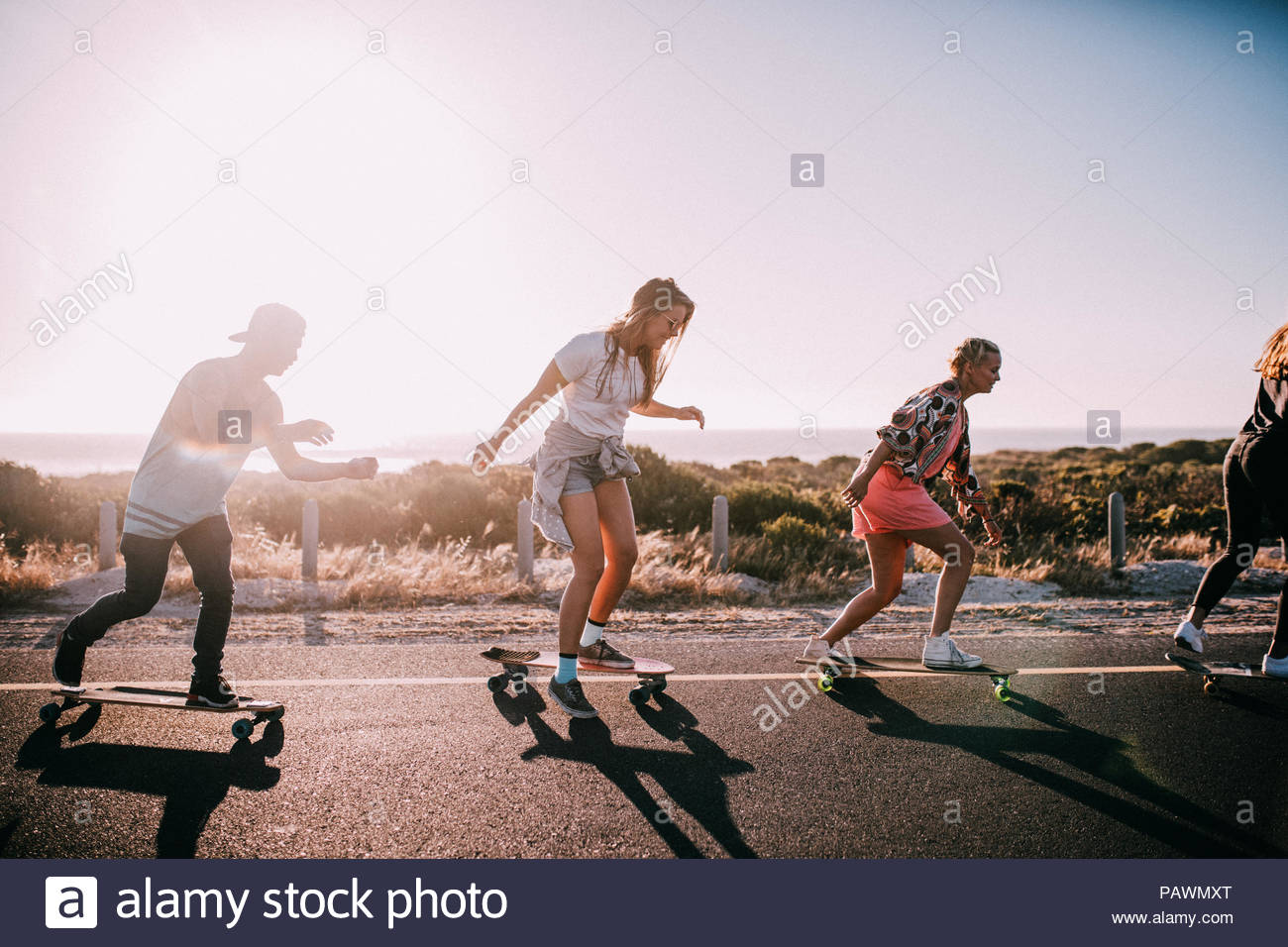 Group of young adult friends cheering and riding longboards - Stock Image