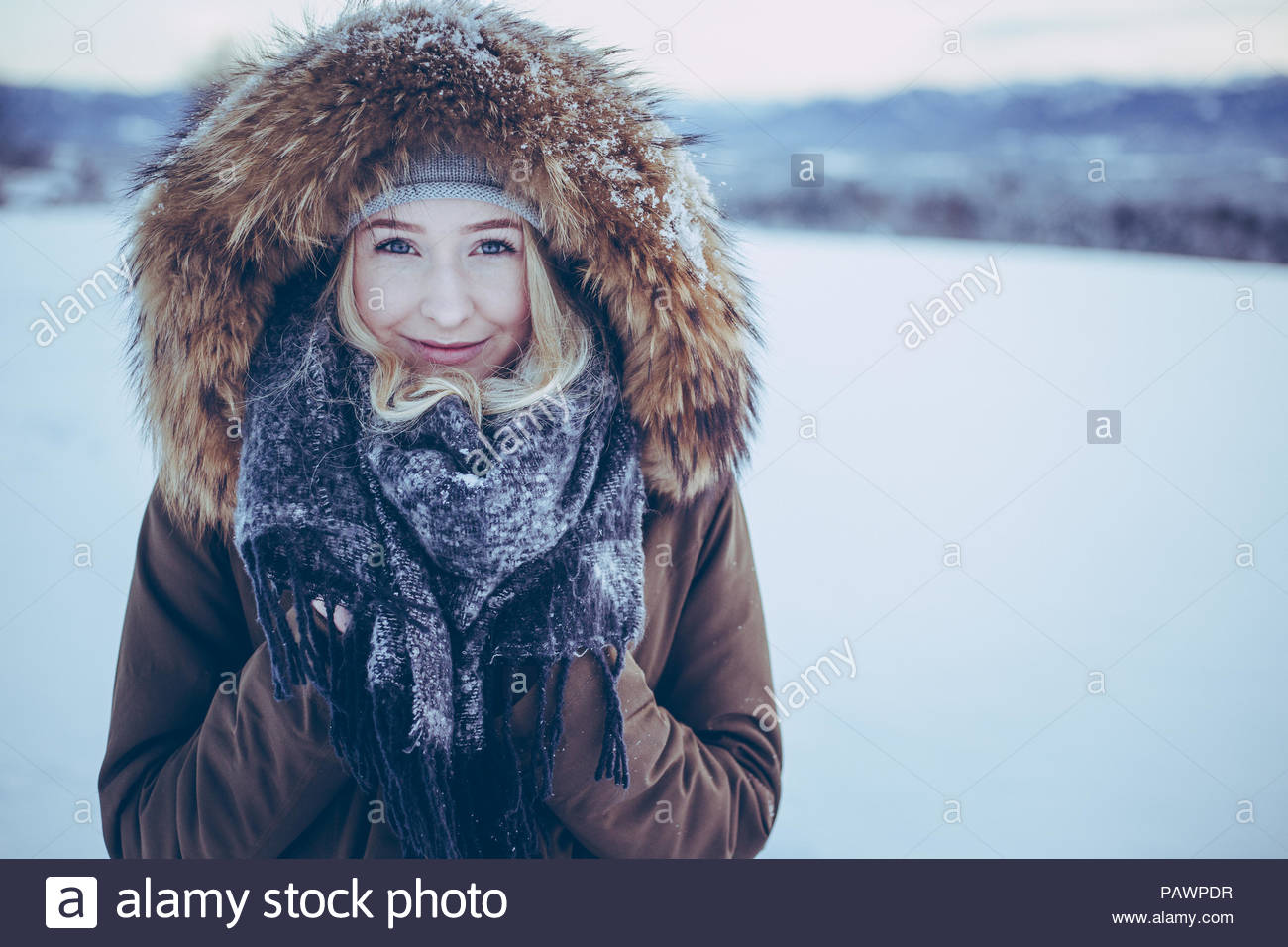Portrait of smiling young woman in the snow during winter - Stock Image
