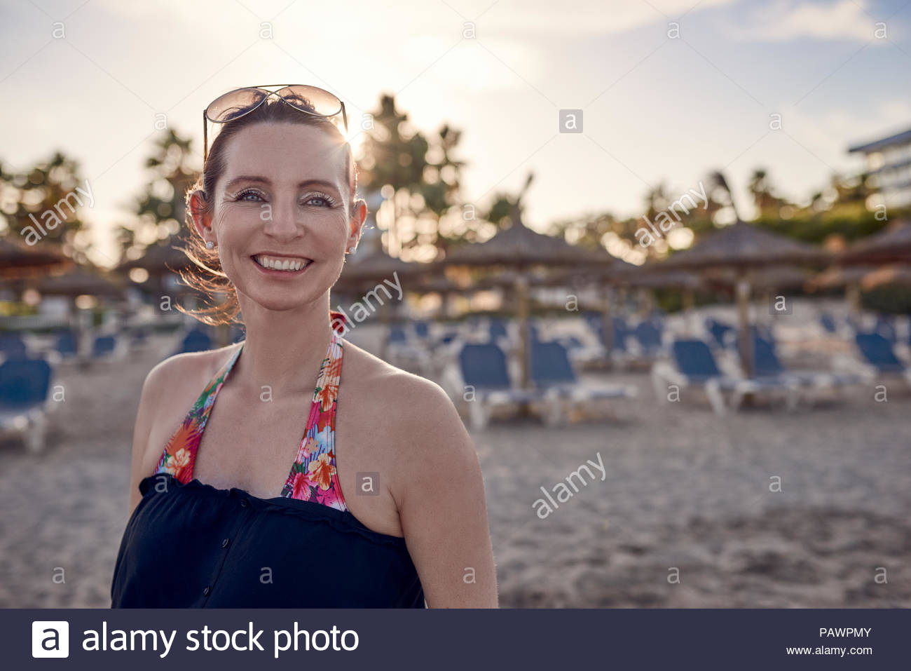 Portrait of smiling young woman at beach - Stock Image