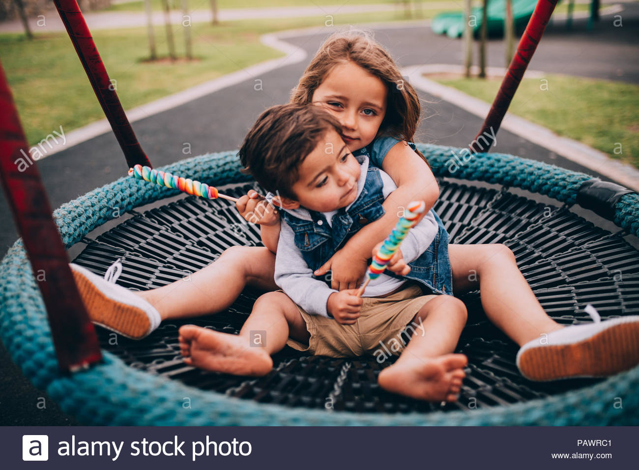Happy children sitting on swing in park - Stock Image