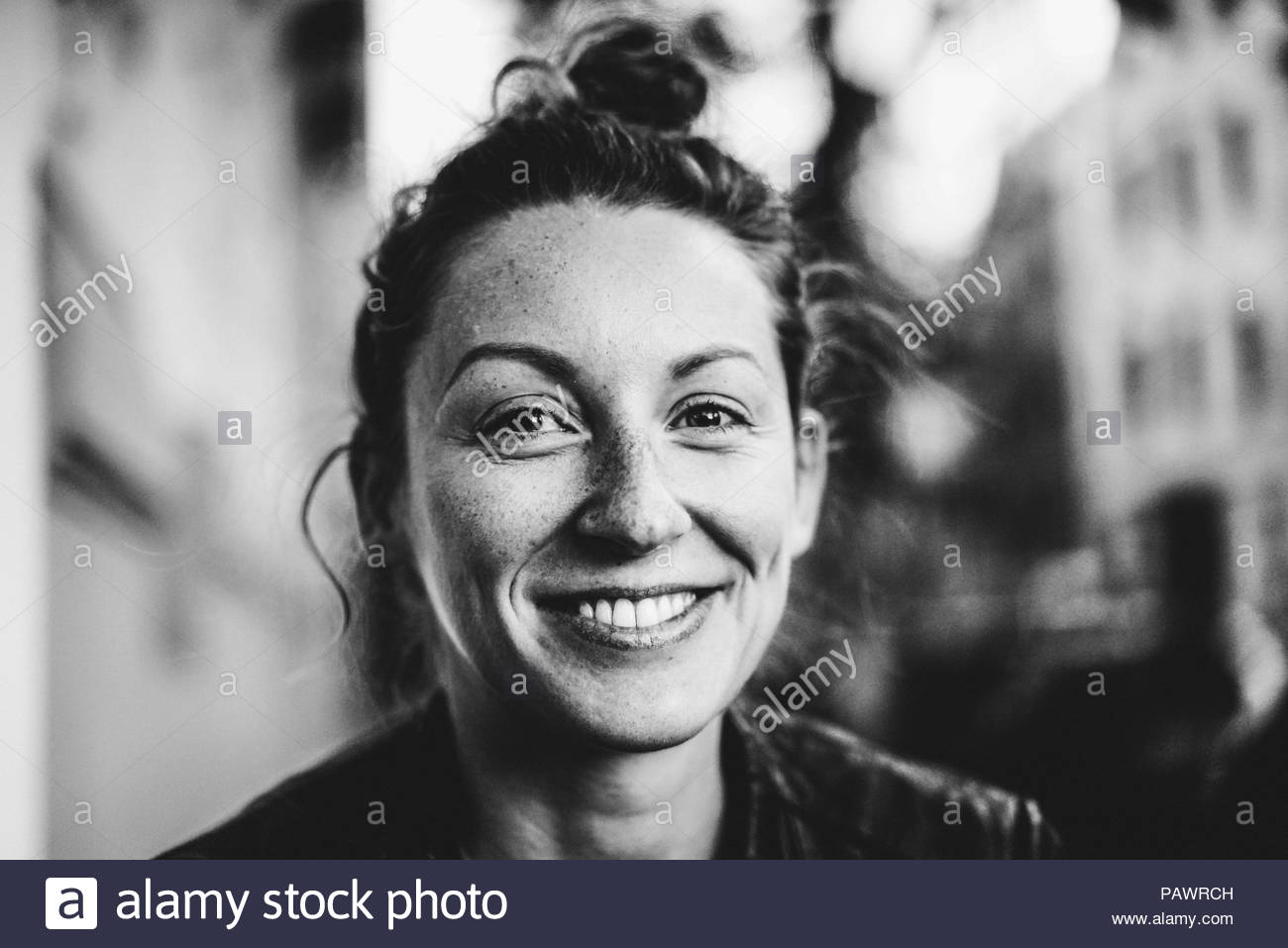 Portrait of a smiling young woman looking into the camera - Stock Image