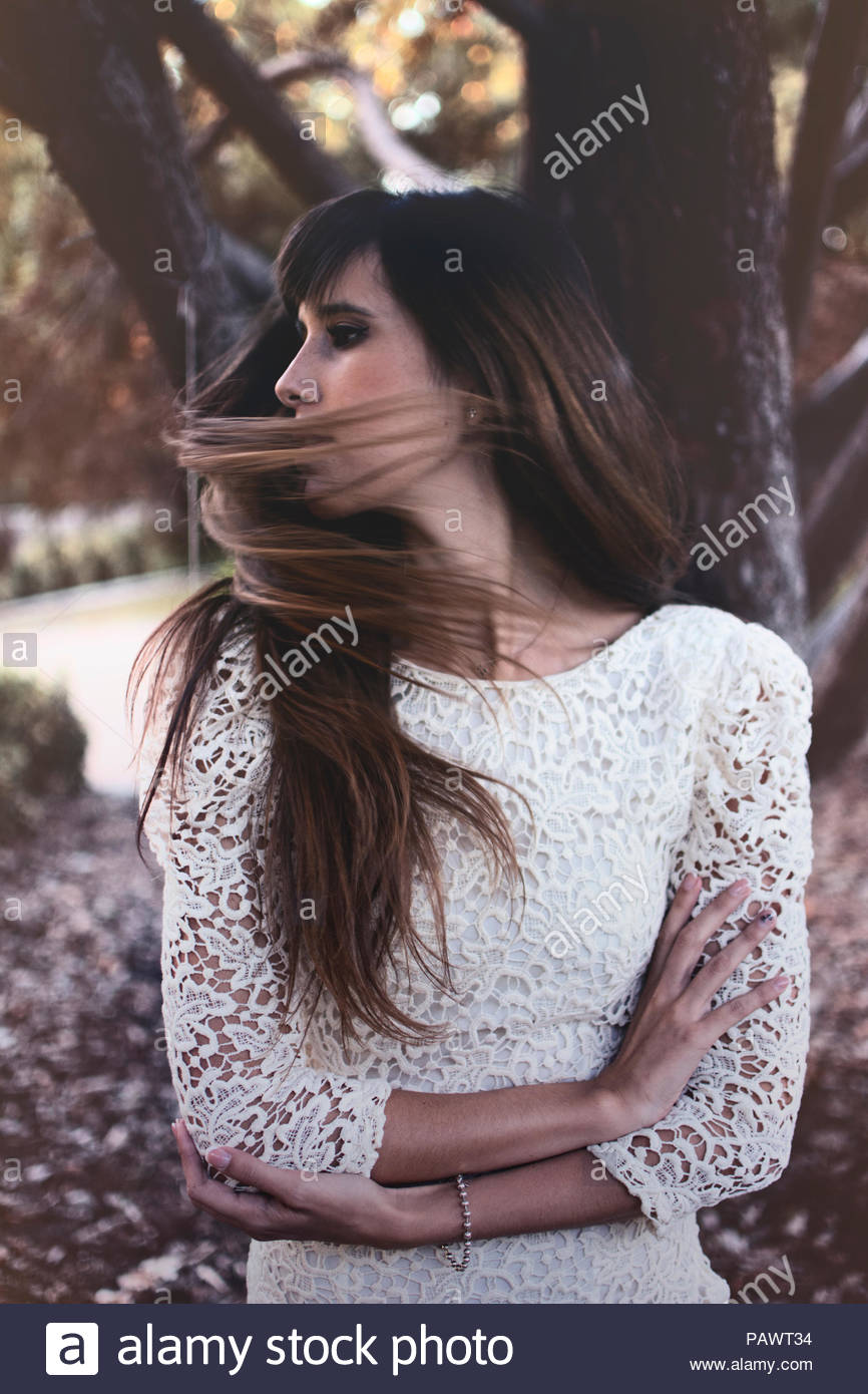 Close-up of young woman with long hair standing by a tree trunk - Stock Image