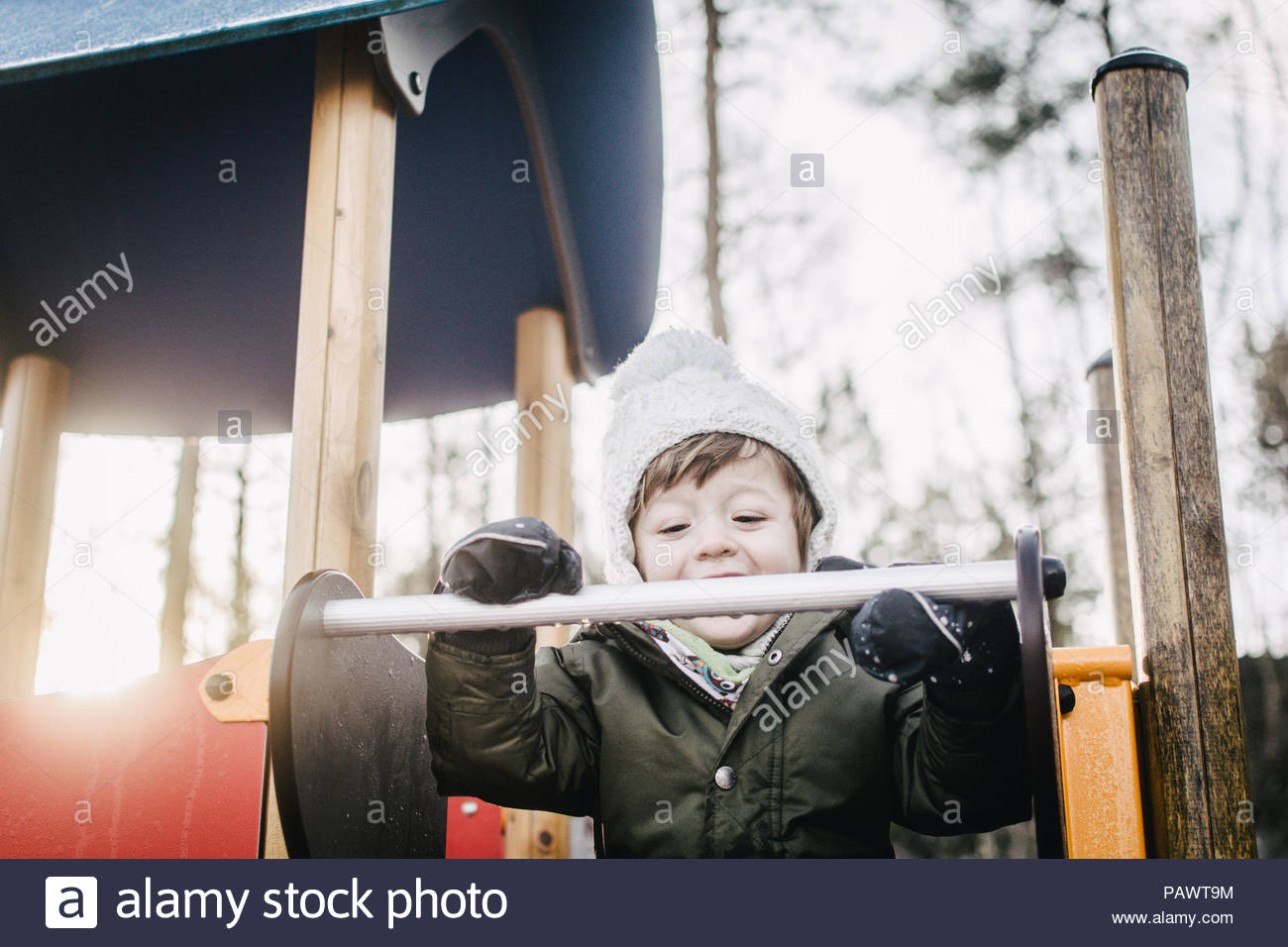 Close up of happy boy playing in snow in the park - Stock Image