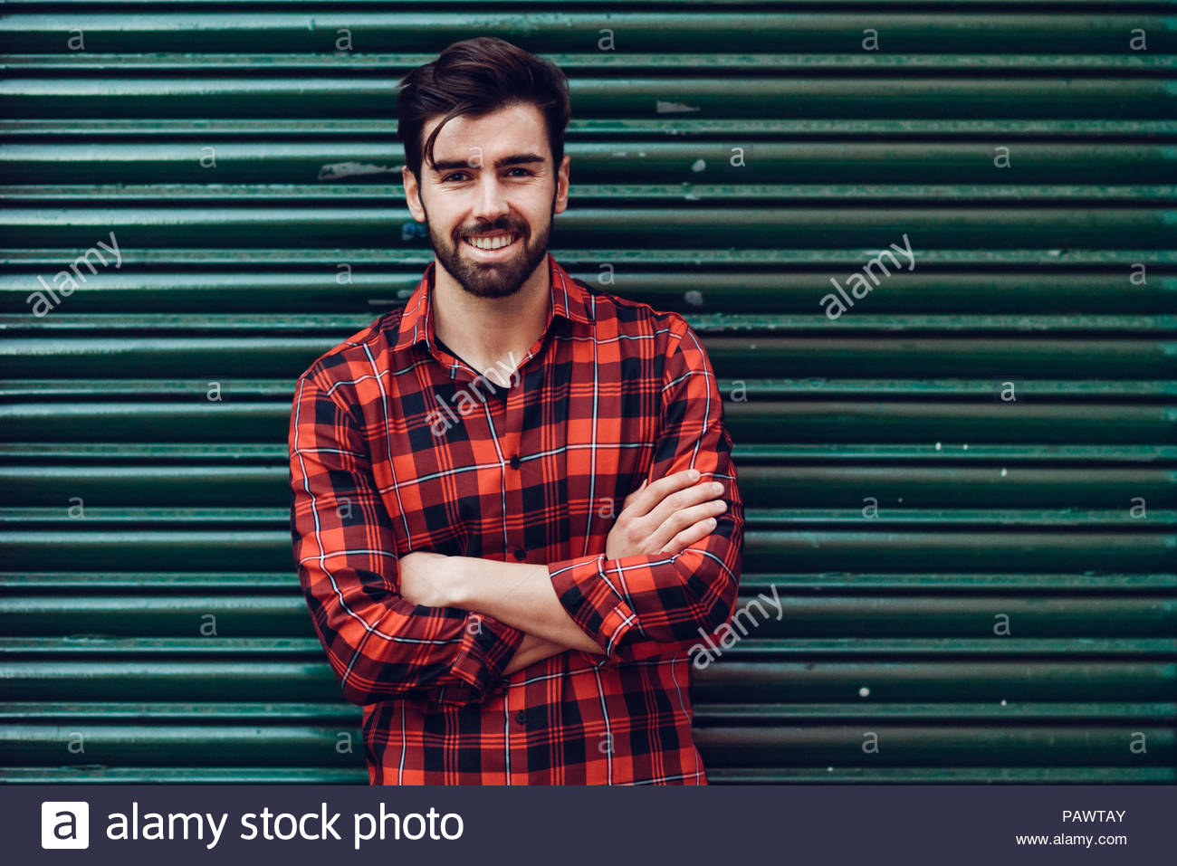 Portrait of a young man standing against a wall looking into the camera - Stock Image
