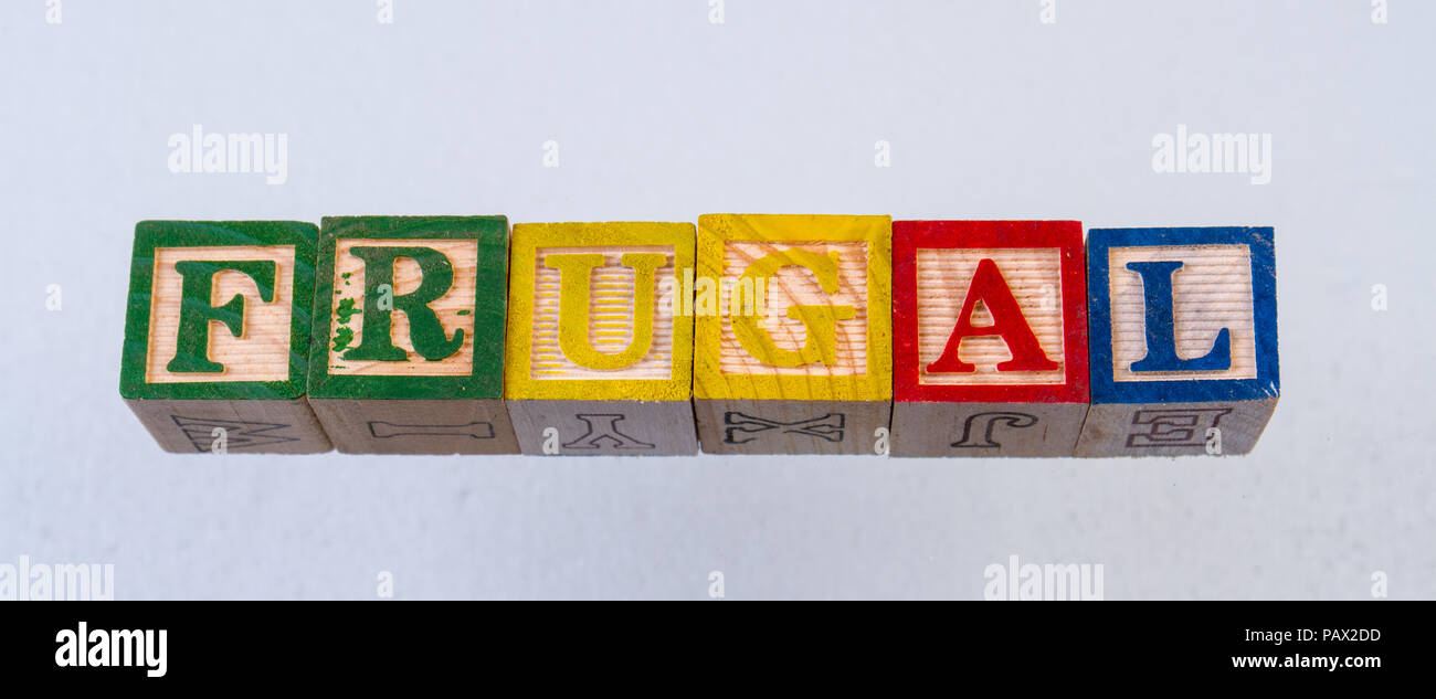 The term frugal displayed visually on a white background using colorful wooden toy blocks - Stock Image