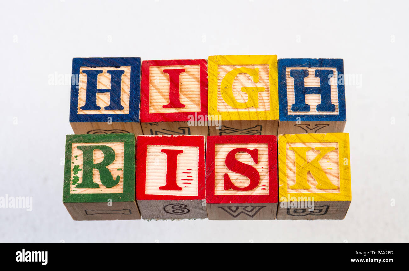 The term high risk displayed visually on a white background using colorful wooden toy blocks - Stock Image