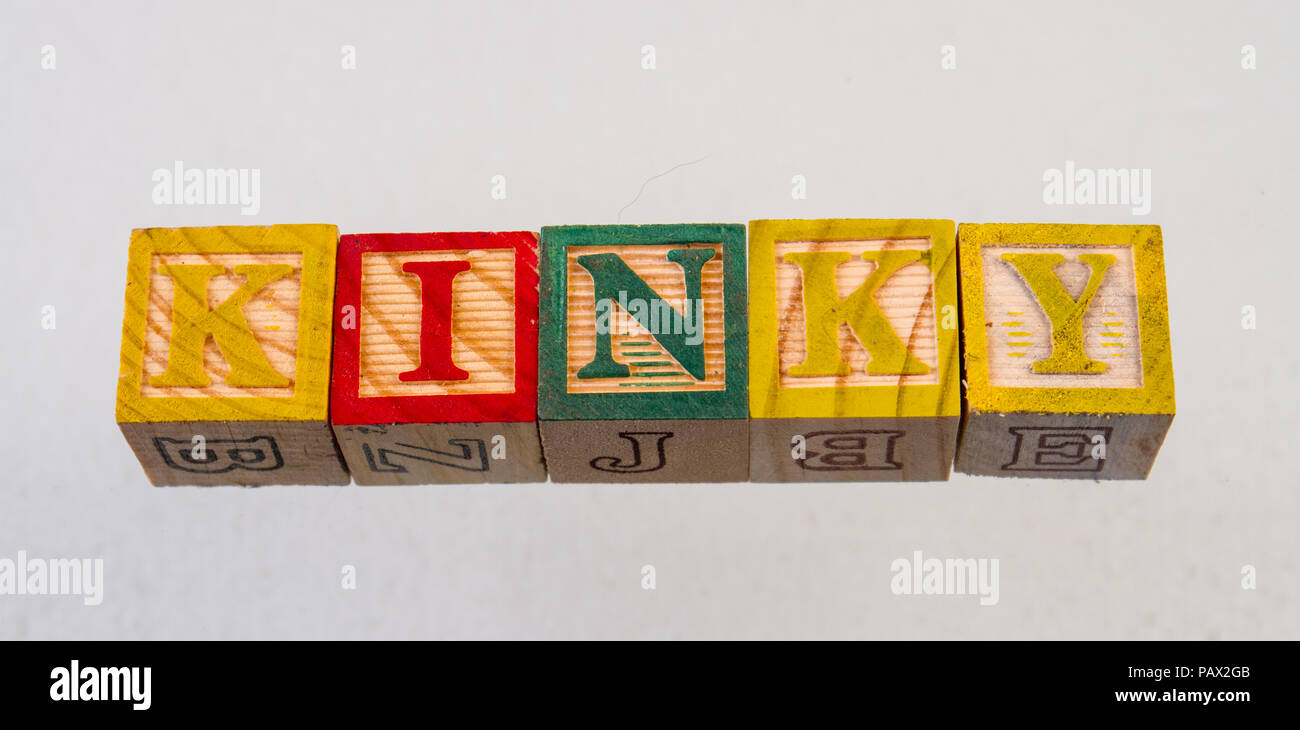 The term kinky displayed visually on a white background using colorful wooden toy blocks - Stock Image