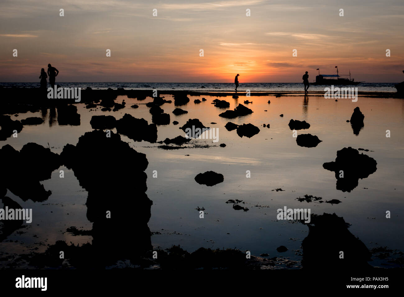 Silhouetted rocky beach scene with locals and tourists collecting starfish and sea-urchins at low tide sunrise - Malapascua Island - Philippines - Stock Image