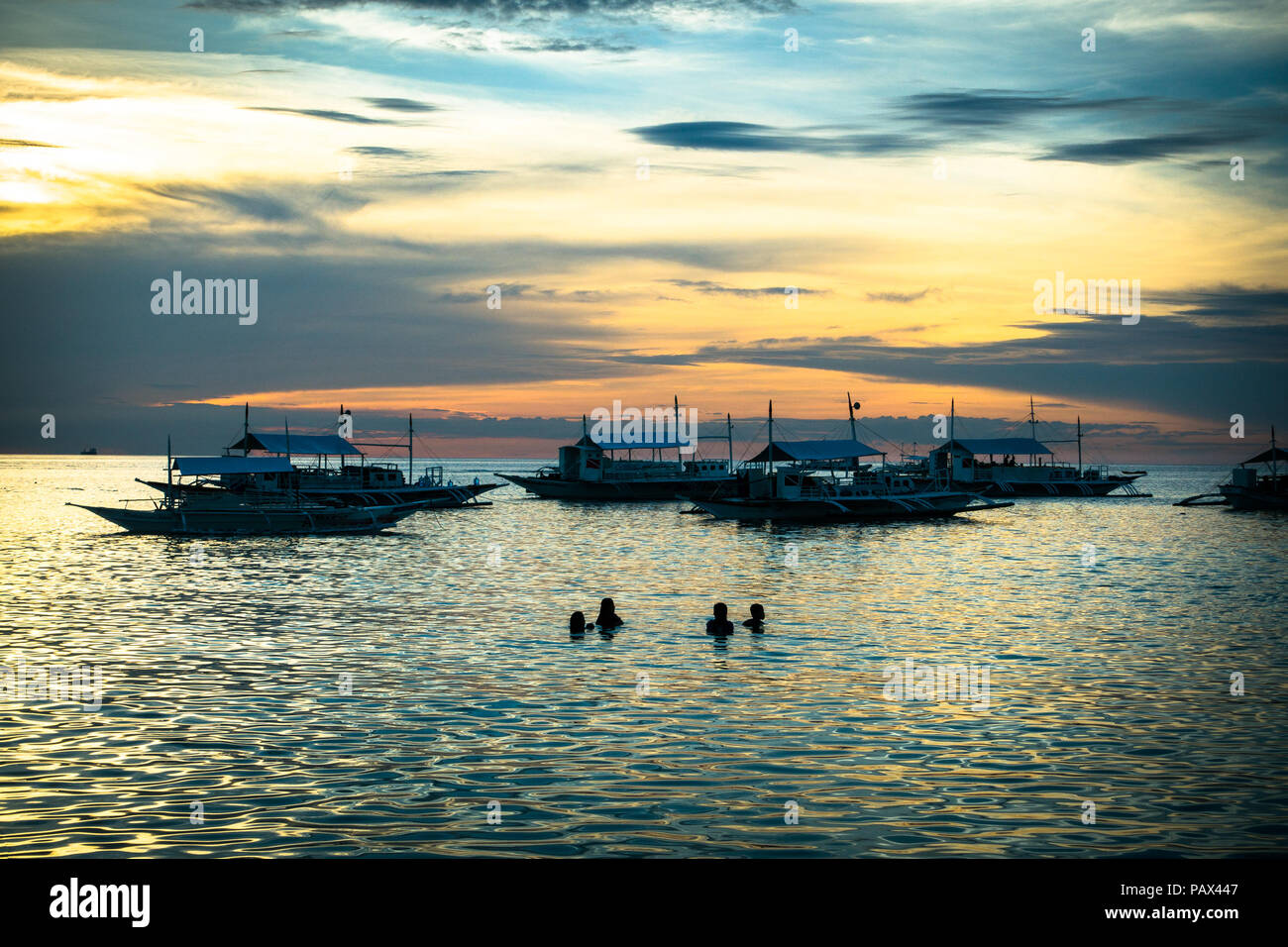 Silhouette of four tourists swimming and playing in the sea near fishing boats at sunset - Malapascua Island, Cebu - Philippines Stock Photo