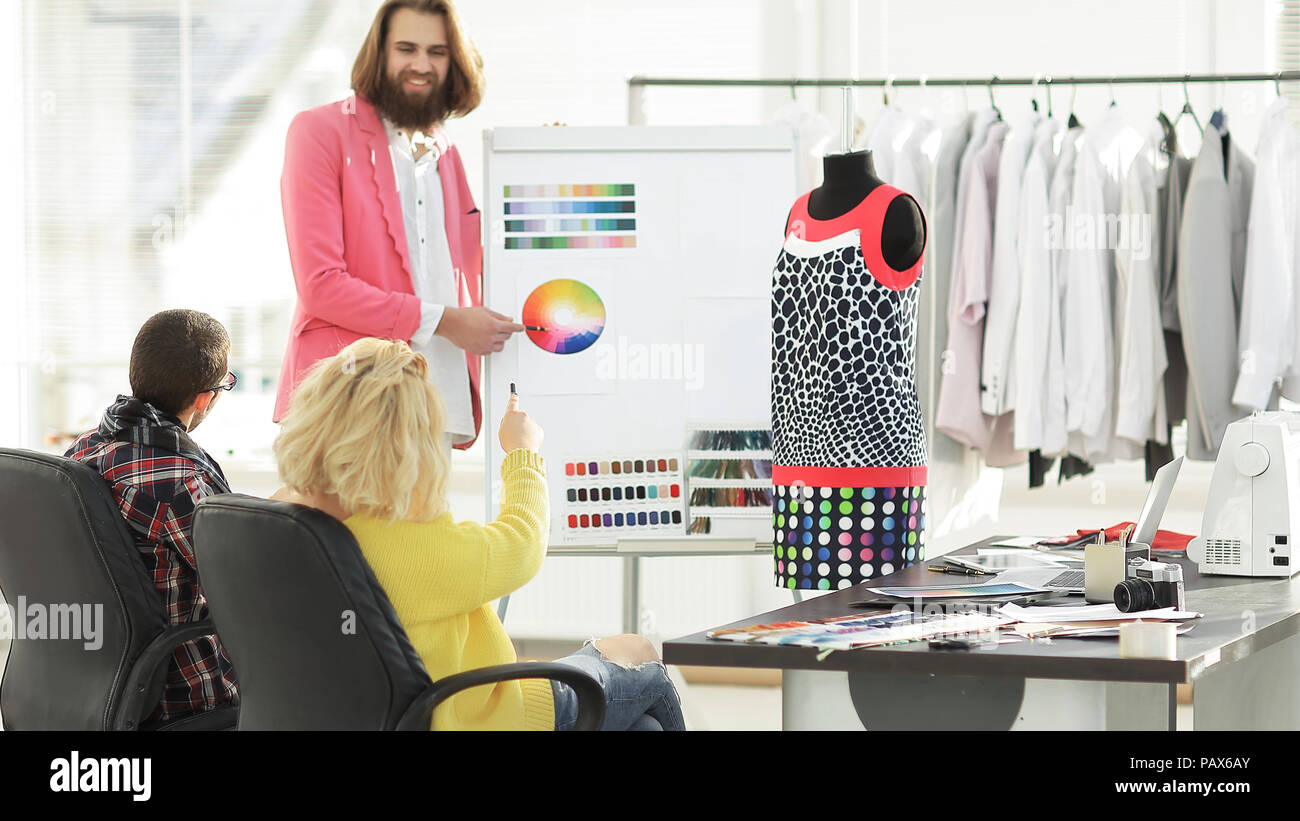 fashion designer showing colleagues the color palette for the new collection - Stock Image