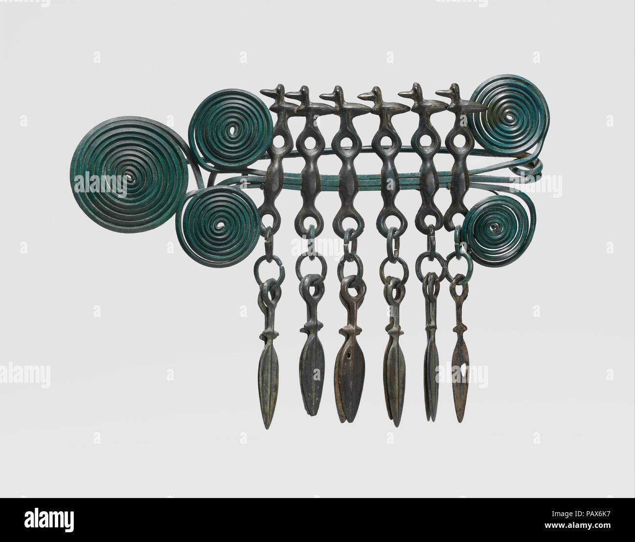Large Brooch. Culture: European Bronze Age. Dimensions: Overall: 11 1/8 x 7 11/16 x 1 11/16 in. (28.2 x 19.5 x 4.3 cm). Date: 1100-1000 BC.  This brooch is one of the largest, most complex objects of its type to survive from late Bronze Age Europe. The five dynamic spirals were composed of three long wires. Hanging from the horizontal section are six composite elements: at the top of each is a bird surmounting a horse bit, beneath which are rings and pairs of dagger blades. The numerous hoards containing such objects suggest that they functioned as ritual offerings deposited during burials.  T - Stock Image