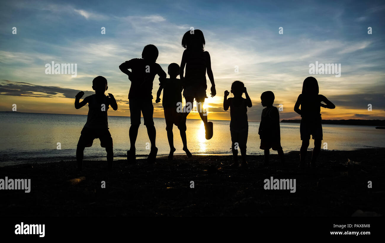 Group Silhouette of Village Children Jumping and Playing on a Sunrise Island Beach - Stock Image