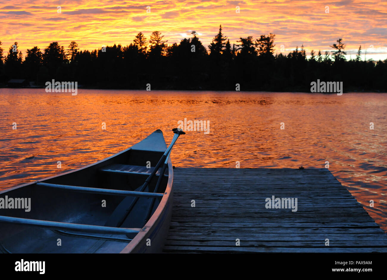 Canoe on dock at sunset sunrise on Lake One in the Boundary Waters Canoe Area near Ely Minnesota - Stock Image