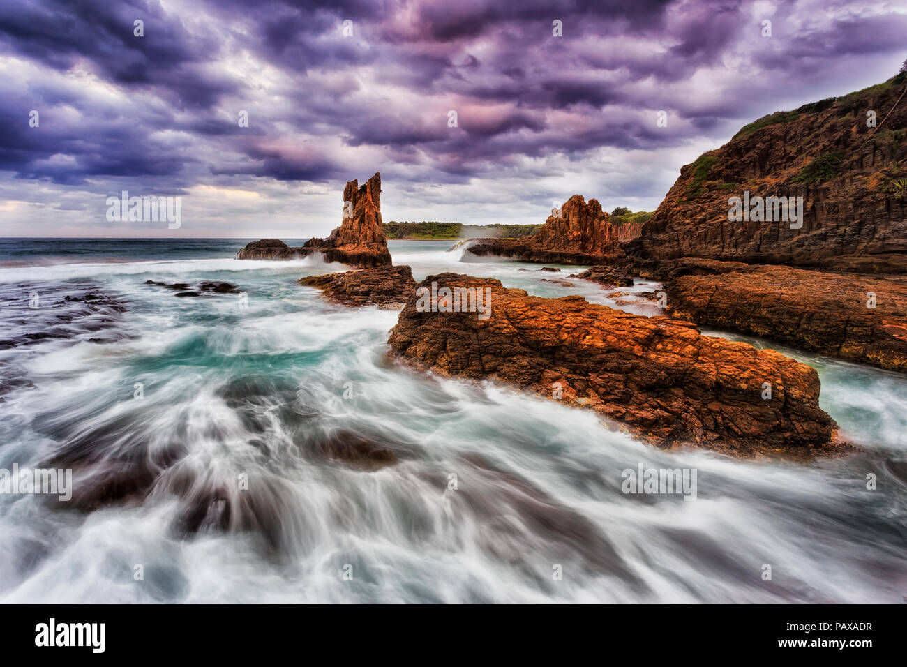 Colourful golden sandstone cathedral rocks at Bombo beach in Kiama, NSW, Australia, at stormy sunset under cloudy sky. - Stock Image