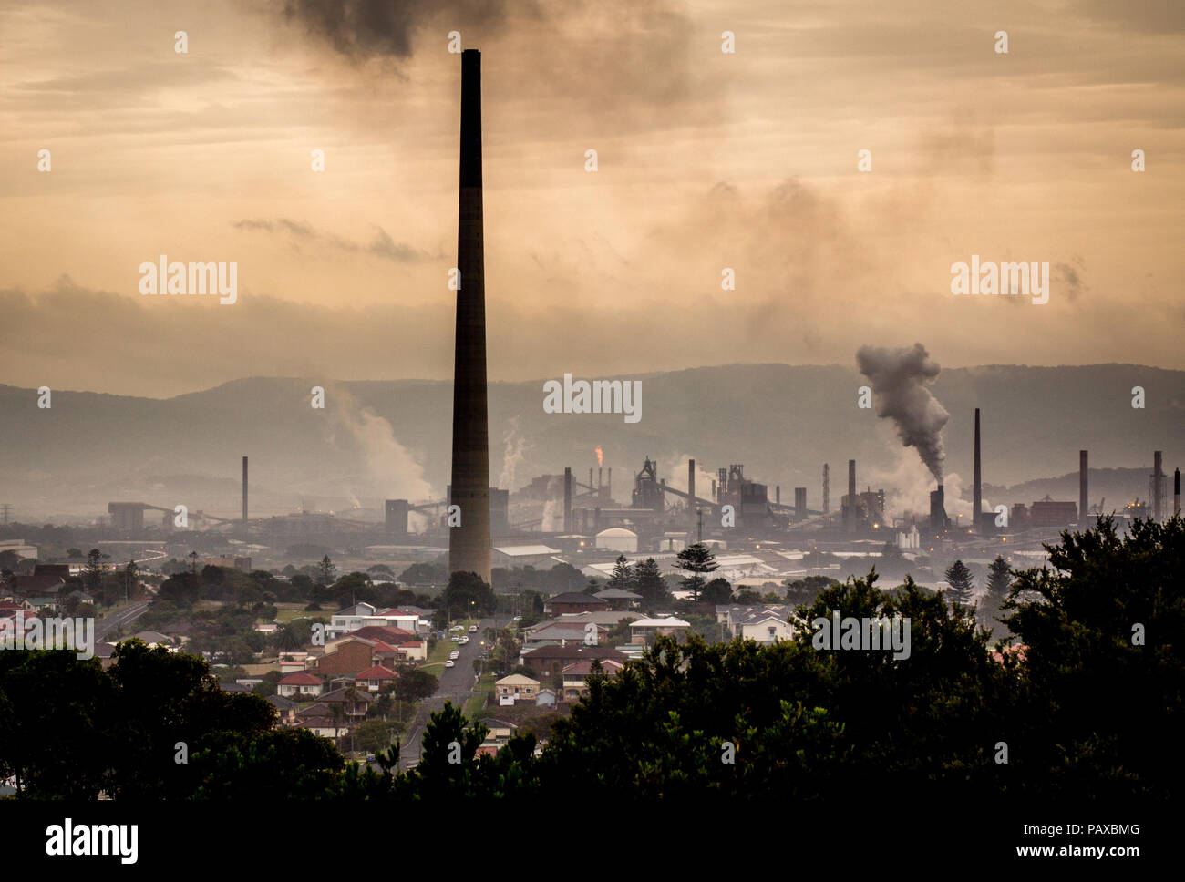 Climate change concept industrial landscape with chimney stacks showing emissions of steam and smoke from industrial works, Port Kembla, NSW Australia - Stock Image