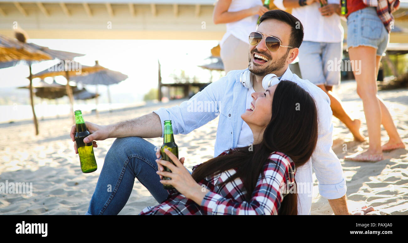 Happy young couple drinking beer and having fun at the beach - Stock Image