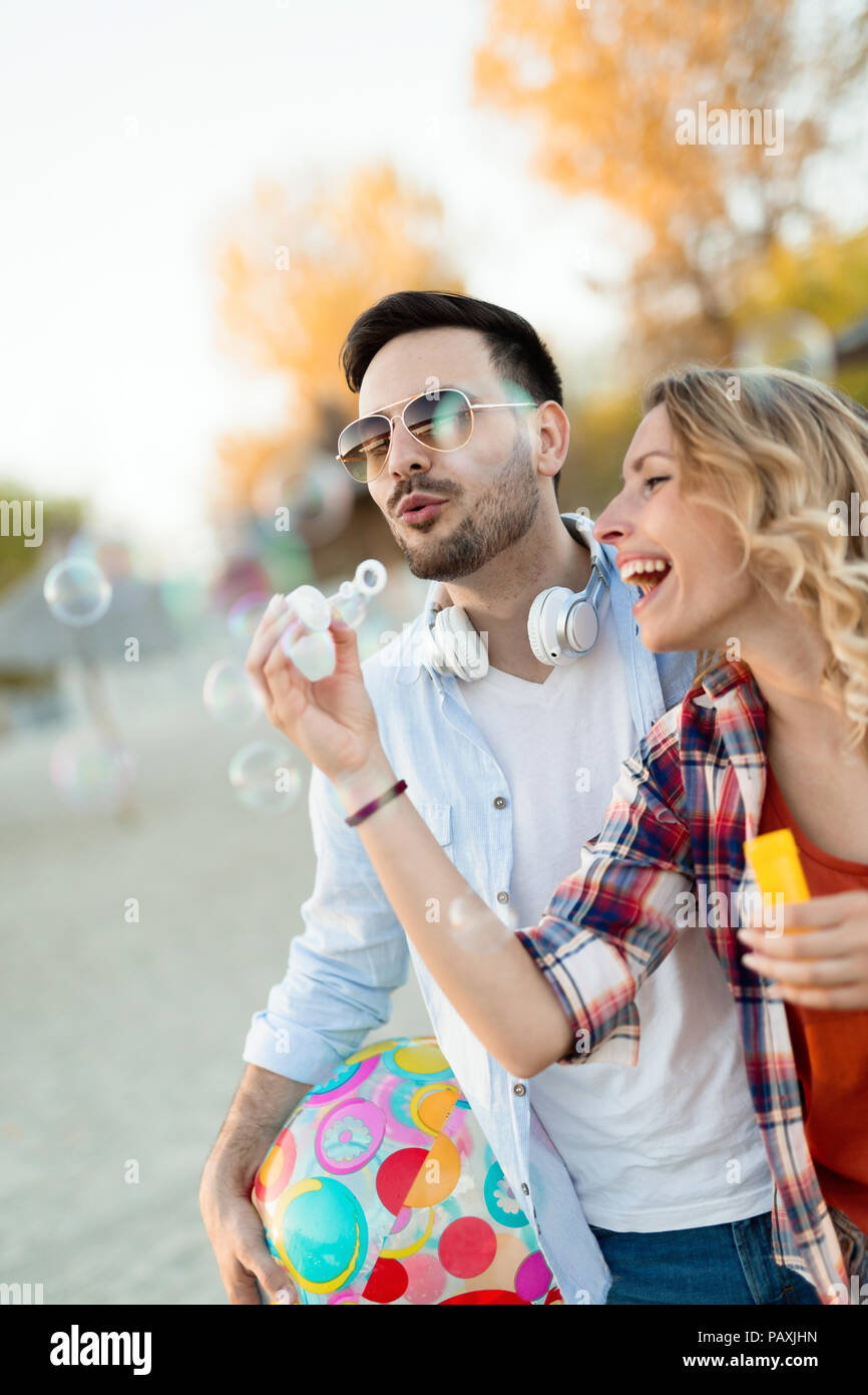 Truly happy playful couple having fun at beach - Stock Image