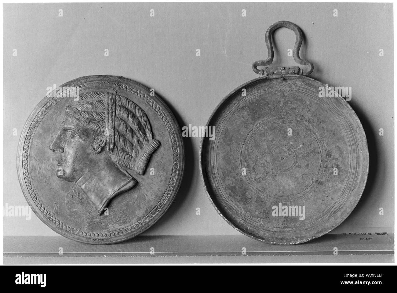 Bronze box mirror. Culture: Greek. Dimensions: diameter  6 1/4in. (15.8cm). Date: mid-4th century B.C..  In relief, head of woman. Museum: Metropolitan Museum of Art, New York, USA. - Stock Image