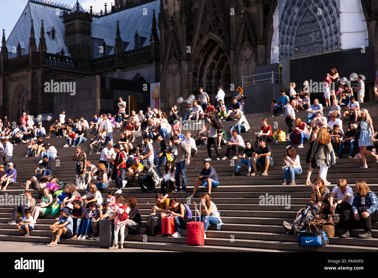 people sitting on the stairs form the cathedral square to the main station, Cologne, Germany.  Menschen sitzen auf der Treppe von der Domplatte zum Ha - Stock Image