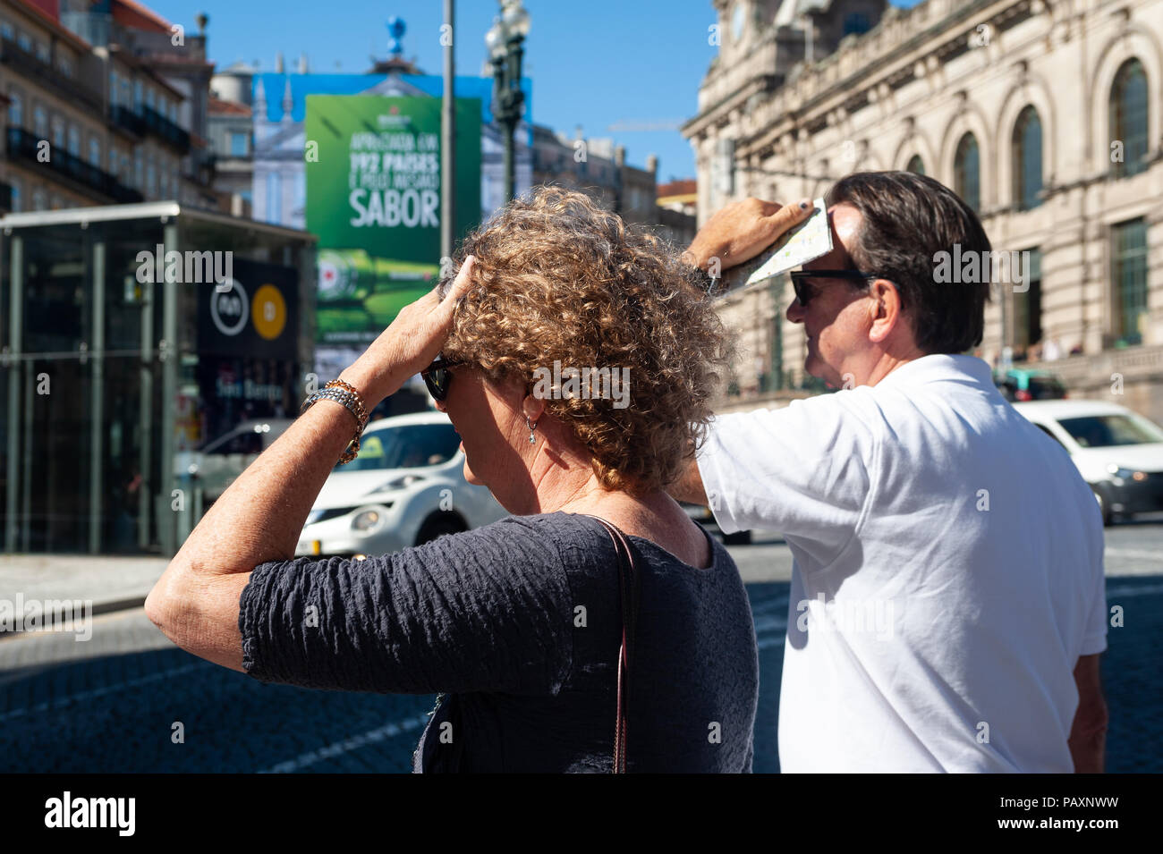 14.06.2018, Porto, Portugal, Europe - Two tourists are seen in Porto's city centre as they shield their faces from the sun. - Stock Image