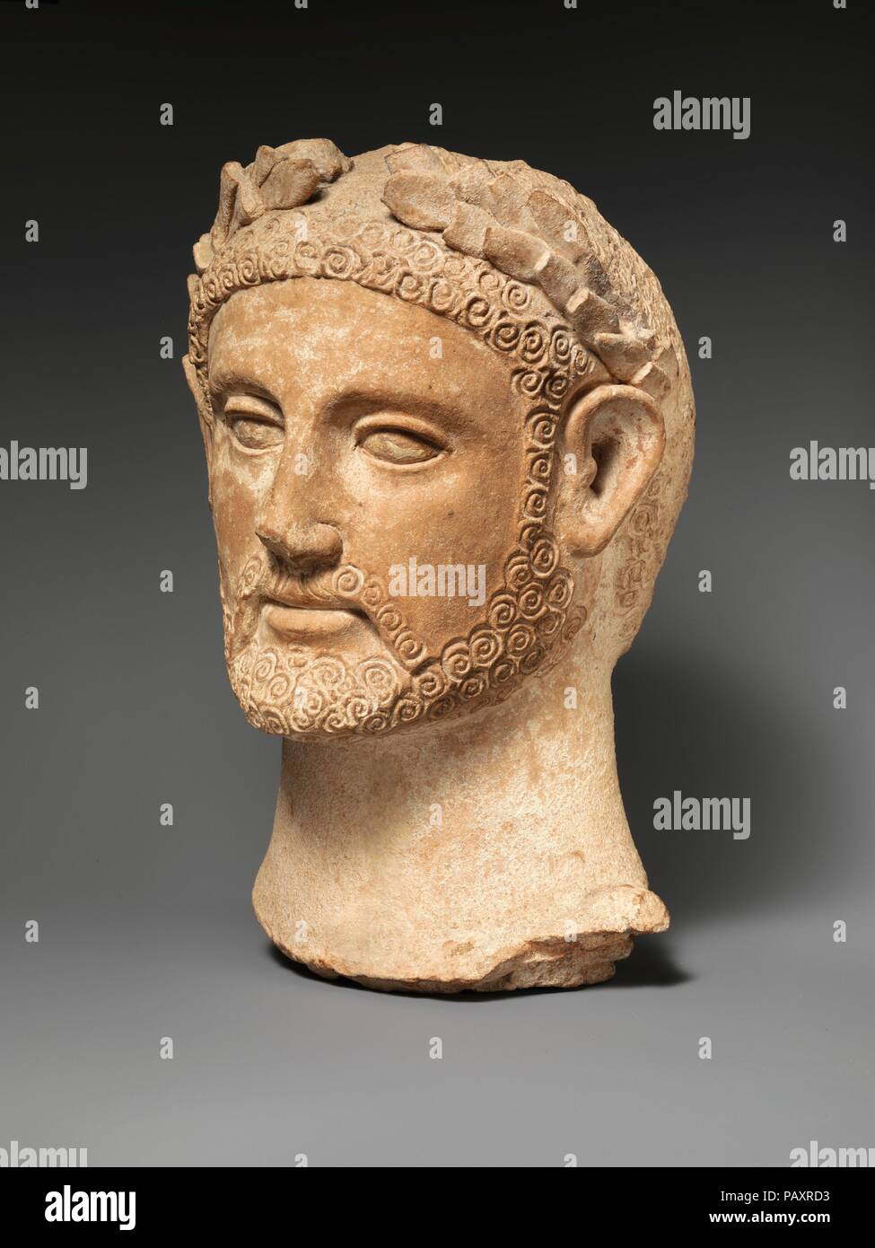 Terracotta head of a man wearing a wreath. Culture: Cypriot. Dimensions: H. 12 1/2 in. (31.8 cm). Date: ca. 400-310 B.C..  Another head made in the same mold is now in the Pierides Museum, Larnaka. It was found in a sanctuary at Pomos in northwestern Cyprus. Museum: Metropolitan Museum of Art, New York, USA. Stock Photo