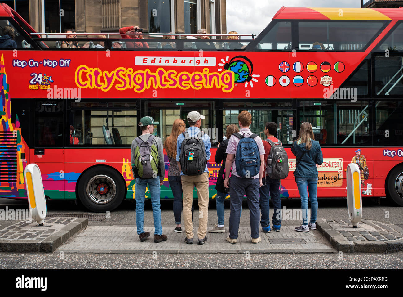 Edinburgh sightseeing bus passing a group of tourists waiting to cross the road in Edinburgh - Stock Image