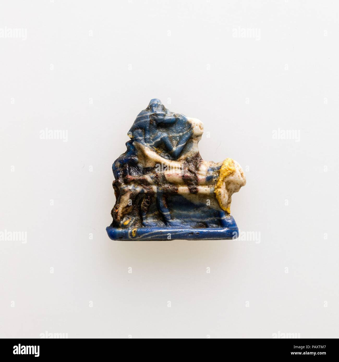Amulet showing  Anubis standing over mummy on bier. Dimensions: H. 2.7 × W. 2.6 cm (1 1/16 × 1 in.). Date: 400-30 BC.  Starting in the later Late Period and continuing through the Ptolemaic Period, a type of glass amulet cast by pressing the glass into a shallow open mold appears. The back was left rough, and the amulets may look ragged because glass overflowed the mold around the edges. The earlier amulets are monochrome, bi- or multicolor amulets supplement the repertoire during the Ptolemaic Period.   Some of the amulets can be specifically tied to spells of the Book of the Dead like this o - Stock Image