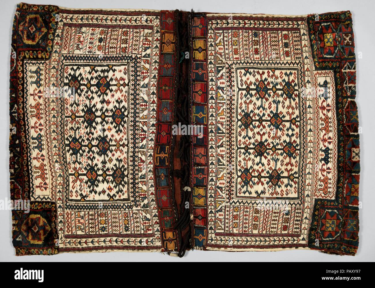 Double Flour Bag. Dimensions: H. 40 1/2 in. (102.9 cm)  W. 56 in. (142.2 cm). Date: last quarter 19th century.  The large double flour bags created by Bakhtiari weavers usually feature pile with symmetrical knots at the bottom to protect the bag in areas of extreme wear. Unlike the other Bakhtiari double flour bag on view (MMA 2015.490.8), the ground here is executed in weft-faced plain weave using white cotton, and the patterning is made in sumak extra-weft wrapping with wool threads. The weaver chose to decorate the bag with repeating lozenges and other geometric motifs, as well as stylized  - Stock Image