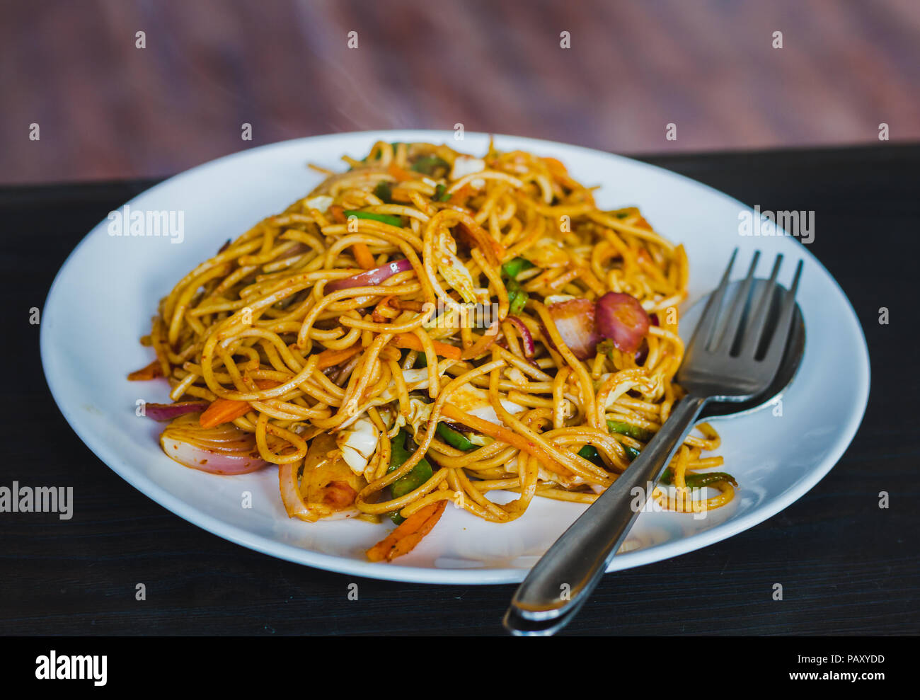 Chinese Noodles, Chowmein on a Plate with Spoon and Fork,Hot and Fresh Chow Mein in Nepali Style Stock Photo