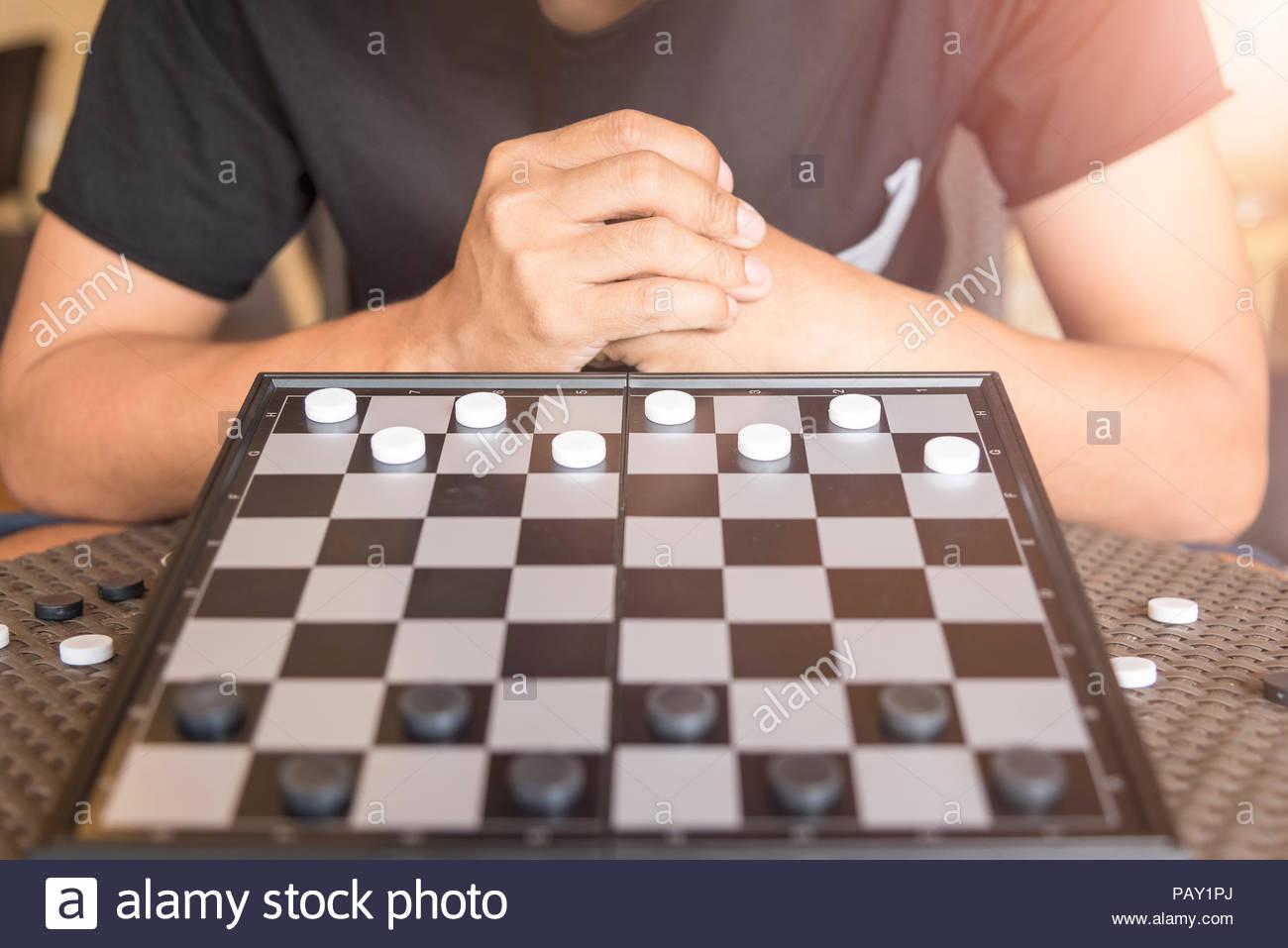 Strategic Planning, Man wear black shirt playing checkers game Stock Photo