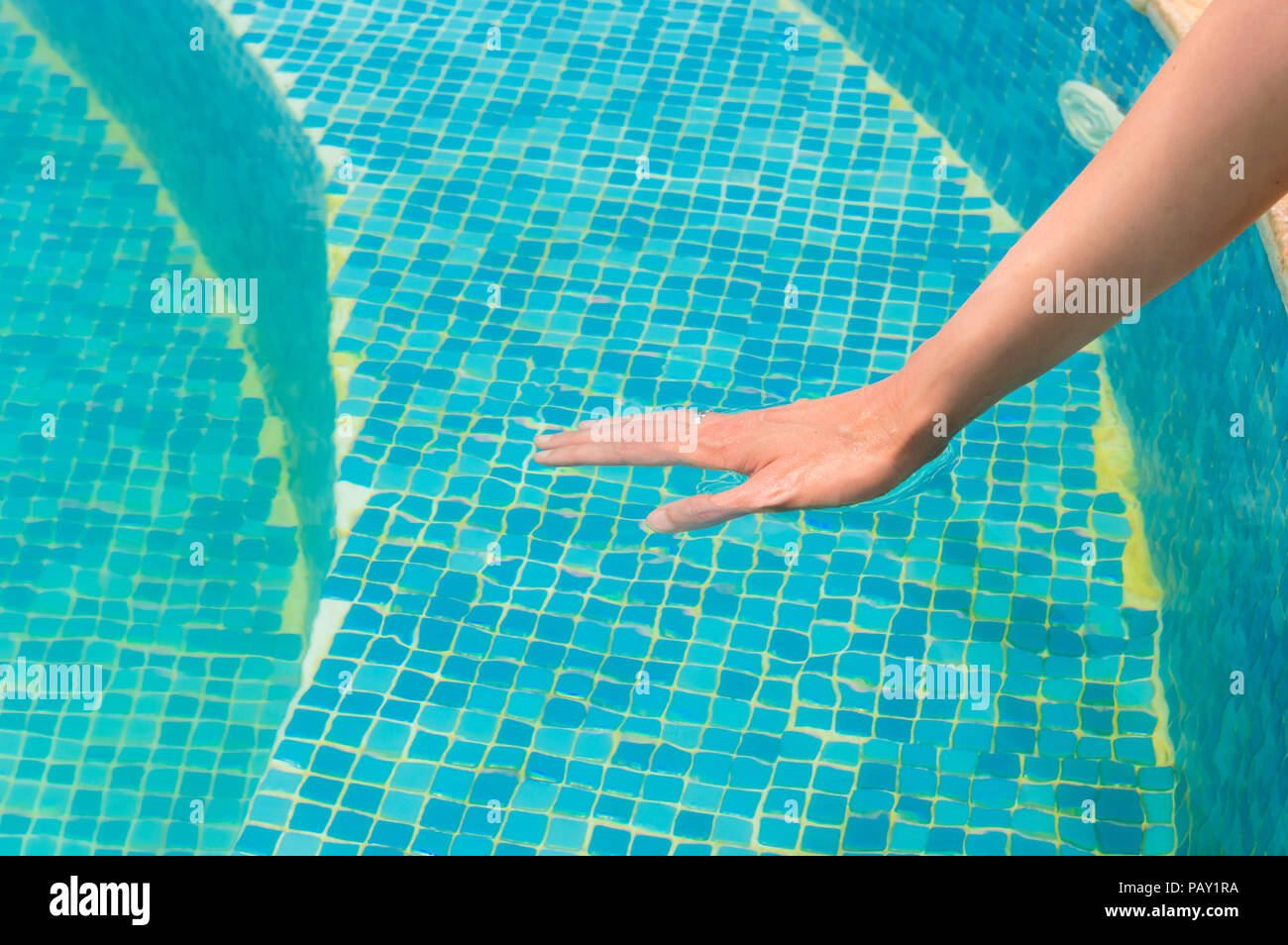 Young woman testing the swimming pool temperature with her hand in the water Stock Photo