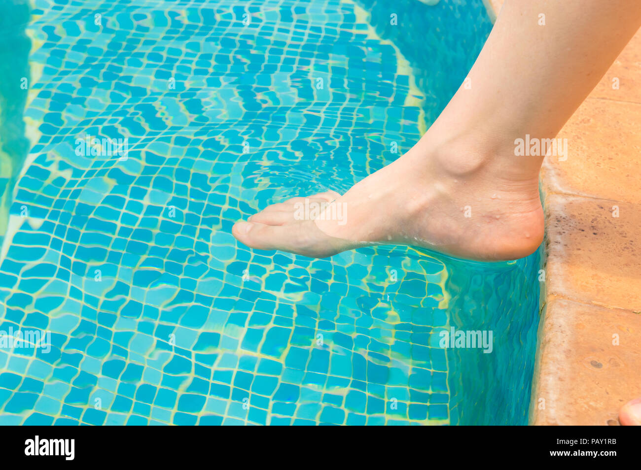 Young woman testing the swimming pool temperature with her foot in the water Stock Photo