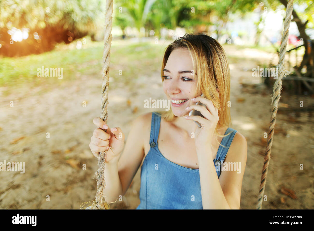 Sunny light portrait of young blonde girl talking by smartphone and riding swing in Bali, sand in background. - Stock Image