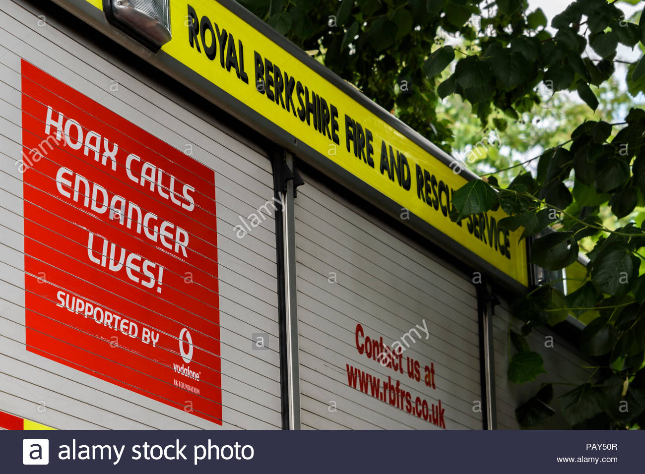 Side on view of a Royal Berkshire Fire and Rescue vehicle advertising Hoax Callers Endanger Lives!, Hungerford, Berkshire, England, UK - Stock Image