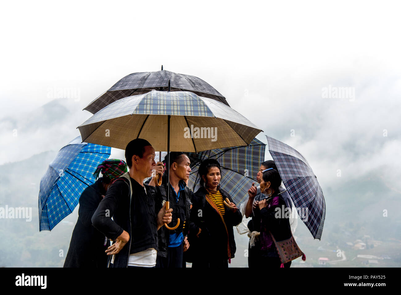 SAPA, VIETNAM - JANUARY 12, 2017: Ethnic Hmong people are under umbrellas because of a strong rain in Ta Van village, Sapa, Vietnam. - Stock Image