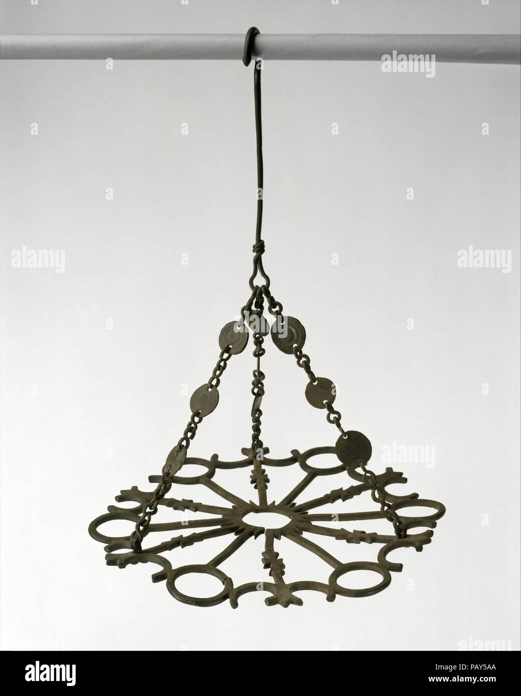 Polycandelon with Crosses. Culture: Byzantine. Dimensions: Ht. with chain 14 in. (35.5cm)  Diam. of plate: 10 7/16 (26.5cm). Date: 500-700.  Round flat hanging lamps, or polycandela, were lit by oil-filled glass vessels hung from the round holes in their designs. Paul the Silentiary in 563 described the effect of huge hanging lamps that lit the great church of Hagia Sophia in Constantinople: 'Thus is everything clothed in beauty...no words are sufficient to describe the illumination in the evening: you might say that some nocturnal sun filled the majestic church with light.'. Museum: Metropoli - Stock Image